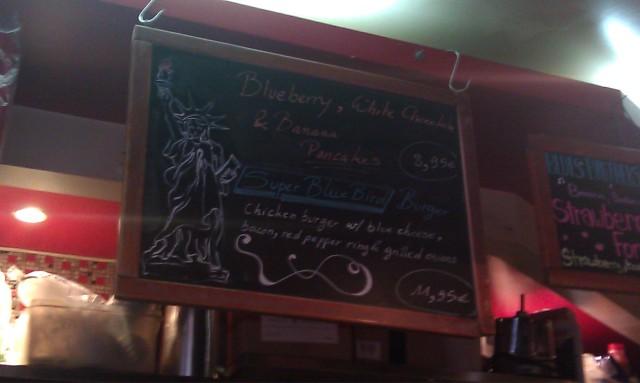 Ardoise indiquant 2 plats spéciaux : pancakes aux myrtilles, chocolat blanc et banane + Super Blue Bird Burger, burger au poulet avec du Bleu, du bacon, un anneau de poivron rouge et des oignons grillés [Slate showing 2 special dishes: Blueberry, white chocolate and banana pancakes + Super Blue Bird Burger, chicken burger with blue cheese, bacon, red pepper ring and grilled onions]